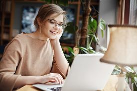 Cheerful Young Caucasian Girl In Glasses Using Laptop, Shopping Online Or Browsing Internet, Chattin