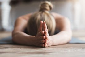 Yoga For Mind. Young Woman Laying Face Down On Yoga Mat At Studio, Meditating