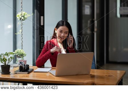 Smiling Business Woman At Work Talking On Phone, Asian Woman Sitting And Working Financial With Lapt