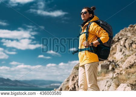 A Female Traveler With A Backpack Against The Sky. Portrait Of A Traveler In Yellow Clothes On The C
