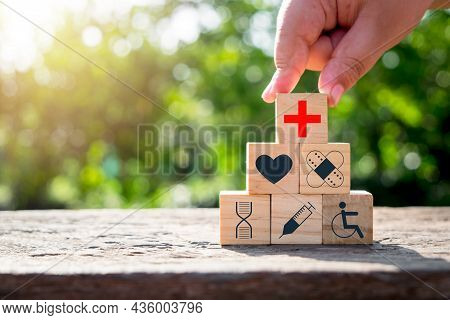 Hand Holding Wooden Block With Icon Healthcare Medical With Copy Space On Green Blurred Backgrounds,