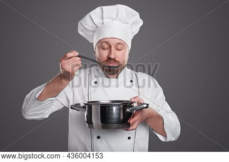 Dreamy Male Cook In White Uniform And Cap Enjoying Scent Of Fresh Dish With Closed Eyes While Standi