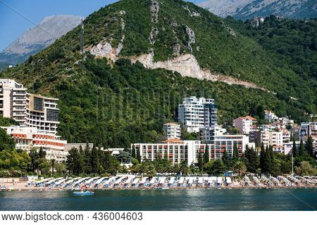 Modern Mediterranean city in Montenegro with resort beach, view from Adriatic sea. Luxury touristic coastline with mountains on background