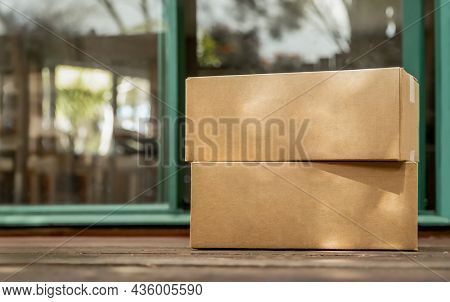 cardboard boxes delivered to the forn door and left outside for contactless pickup, delivery for online shopping, contact-free delivery and pickup due to COVID-19. High quality photo