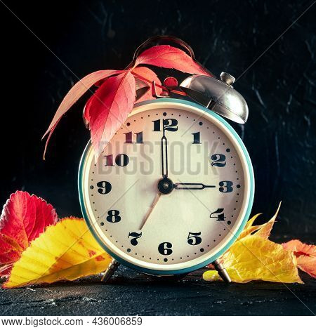 Daylight Saving Time Concept, Fall Back One Hour In Autumn. A Vintage Alarm Clock With Autumn Leaves