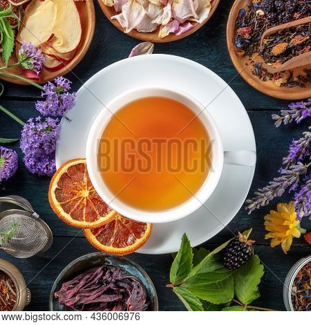 Tea, Overhead Square Shot. Leaves, Flowers And Fruit Around A Cup Of Tea On A Dark Rustic Wooden Bac