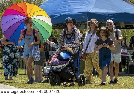 Eungella, Queensland, Australia - October 2021: Girl With A Vibrant Rainbow Colored Umbrella Walks W