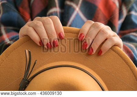 Stylish Red Female Nails. Woman In Poncho Holding Brown Trendy Hat. Modern Beautiful Manicure. Autum