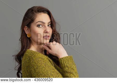 Close-up Portrait Of Beautiful Sensual Woman With Long Curly Hair Against Gray Background