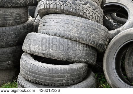 Pile Of Old Dirty Worn-out Rubber Tire Tires On The Grass. Concept Of Illegal Landfills Of Rubber Ti