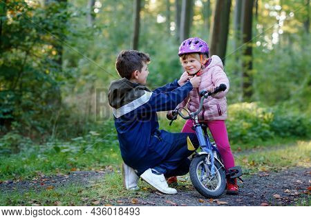 School Kid Boy, Brother Put On Little Preschool Sister Girl Bike Helmet On Head. Brother Teaching Ha