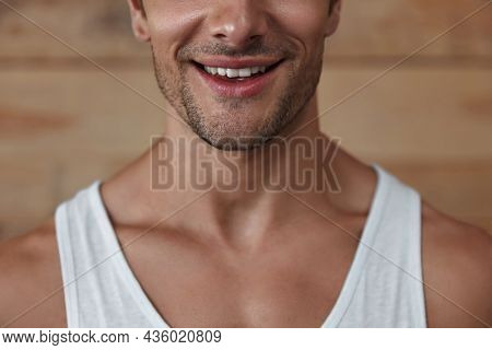 Partial image of young smiling man. Handsome brown hair muscular guy wearing tank top. Summer season. Isolated on wooden background. Studio shoot