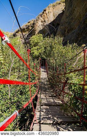 Long old wooden walking swing bridge over river in Los Cahorros Granada, Spain