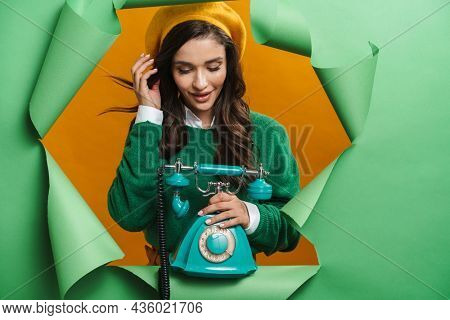 Young white smiling woman peeking out hole isolated on green background holding landline phone