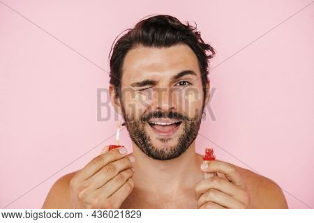 White shirtless man winking while applying concealer isolated over pink background
