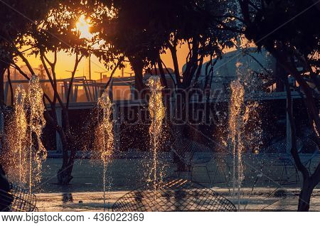 Sunset City Fountain With Frozen Water Drops