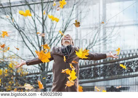 A Happy And Successful Businessman In A Brown Coat Throws Yellow Maple Autumn Leaves In A City Park