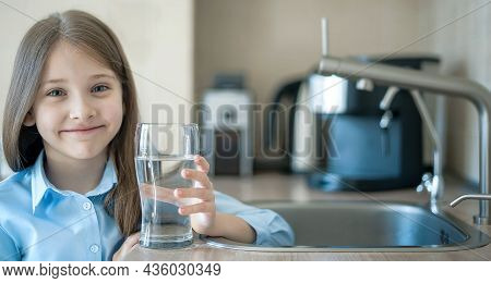 A Glass Of Clean Water In Kids Hands. Caucasian Little Girl Drinking From Water Tap Or Faucet In Kit