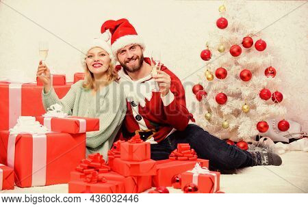 Celebrating Christmas Together. Loving Couple Cuddle And Drink Champagne Near Christmas Tree. Couple