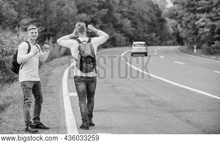 Travel By Autostop. Hopeless Hitchhiker. Men Try Stop Car. Twins Walking Along Road. Hiker Man On Ro