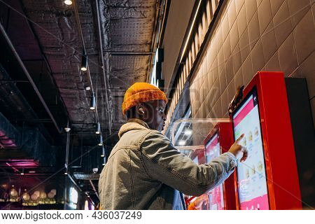Smiling African-american Man In Warm Denim Jacket With Wireless Earphones Uses Self-service Kiosk To