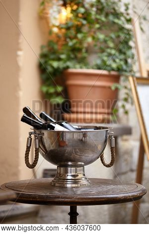 Wine Bottles In A Large Metal Bowl Standing On Wooden Table On The City Street To Attract Visitors T