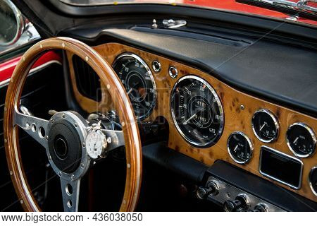 Cockpit Of A Classic Convertible Sports Car With Burl Wood Analog Gauges And Steering Wheel