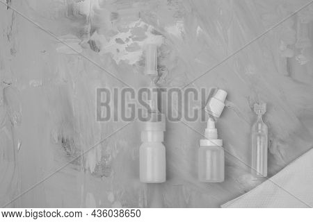 Different Types Of Medical Drops, Nasal Spray On Grey Stone Background. Sanitation Of The Nose, Rins