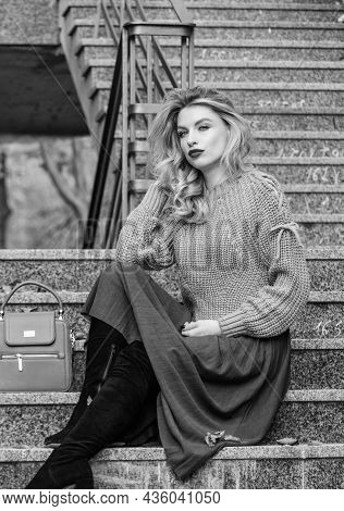 How To Style Sweater And Skirt Combo For Fall. Woman With Gorgeous Hairstyle Sit On Stairs Outdoors.