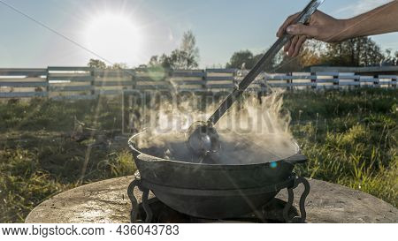 Camping Stove And Steam Coming Out Of The Bowl In A Sunny Day With Blue Sky During Camping Adventure