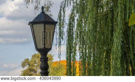 Lantern Against Autumn Yellow Trees. Street Lamp In The Autumn Park. Beautiful Autumn Landscape With