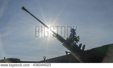 Piece Of An Anti-aircraft Artillery Batteries Against The Background Of Blue Sky And Sun At Sunset.