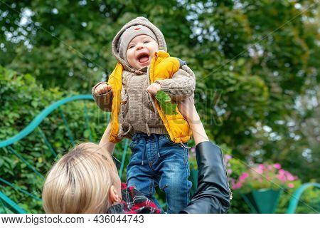 Happy Mother Playing With A Small Son, Throwing In The Air, Outdoors In Autumn Park. Mom Throws Her