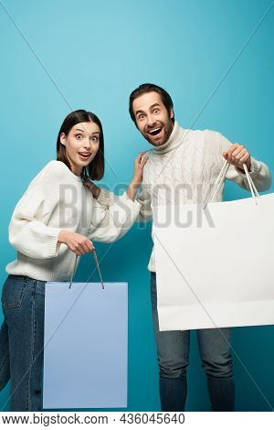 Astonished Couple With Shopping Bags Looking At Camera On Blue