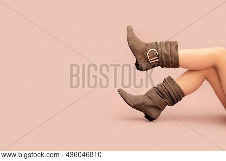 Beautiful Caucasian Sexy Woman's Legs In Beige Brown Suede Short Wide Ankle Buckle Boots Without Hee