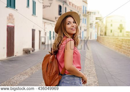 Traveler In Sardinia. Young Stylish Tourist Woman Walking On The City Street Looking Back Camera Smi