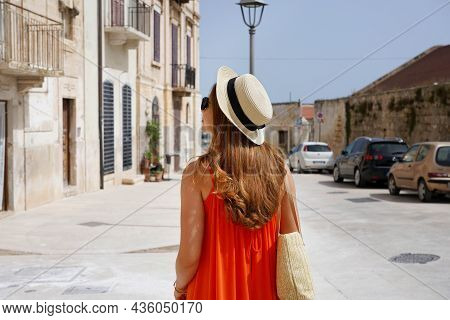 Back View Of Tourist Woman Visiting Historic Town In Apulia, Italy