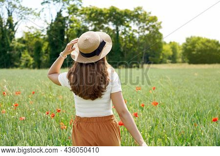 Back View Of A Young Woman Who Regenerates Herself Walking In The Nature