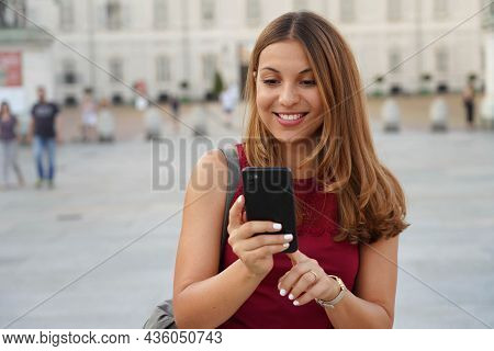 Hispanic Young Woman Walking In The Street Paying Online For E-commerce On Her Mobile Phone
