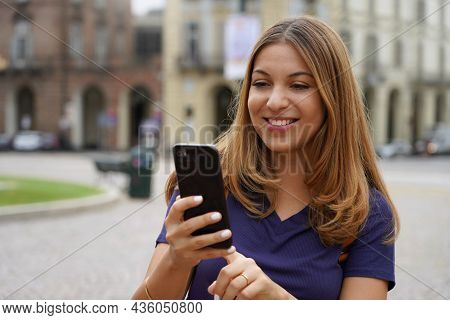 Close-up Portrait Of Young Smiling Woman Using Smartphone Outdoors