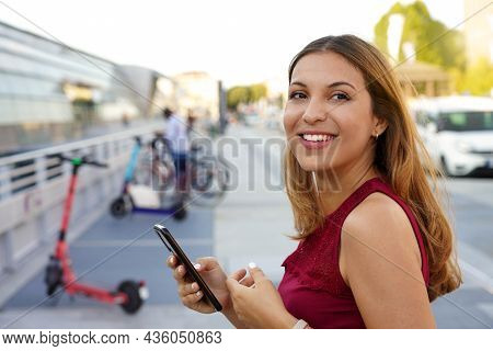 Close-up Of Confident Young Business Woman Turns Around And Smile Using Smartphone App She Is Prepar