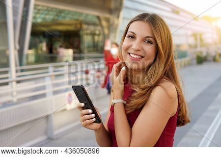Young Female Model With Long Hair Looks At The Camera Holding A Mobile Phone Outdoors