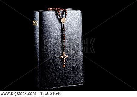 Bible With Wooden Rosary Beads And Crucifix Isolated On A Black Background