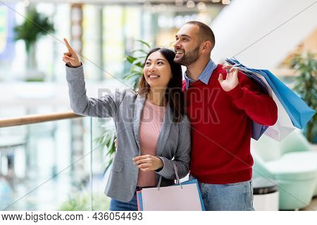 Shopping Together. Millennial Interracial Couple Buying Goods At Supermarket, Holding Shopper Bags,