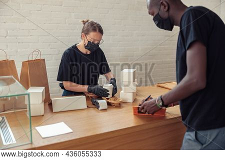 Black Man Writing Date Of Visitors In Notebook