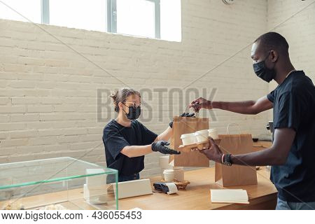 Barista Handing Over Food For Delivery To Deliveryman