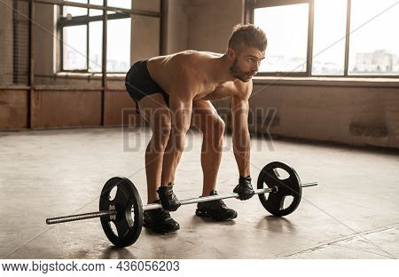 Full Length Of Concentrated Athletic Shirtless Bearded Male In Weightlifting Gloves Deadlifting Heav