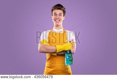 Excited Comic Male Cleaner In Apron And Rubber Gloves Standing With Liquid Detergent On Violet Backg