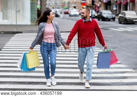 Full Length Portrait Of Young Multiracial Couple With Shopper Bags Crossing Street, Holding Hands Ou