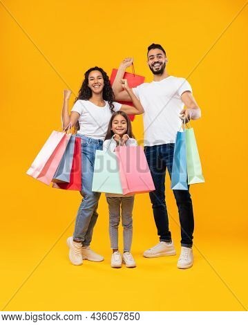 Middle-eastern Family Holding Shopping Bags Standing On Yellow Studio Background